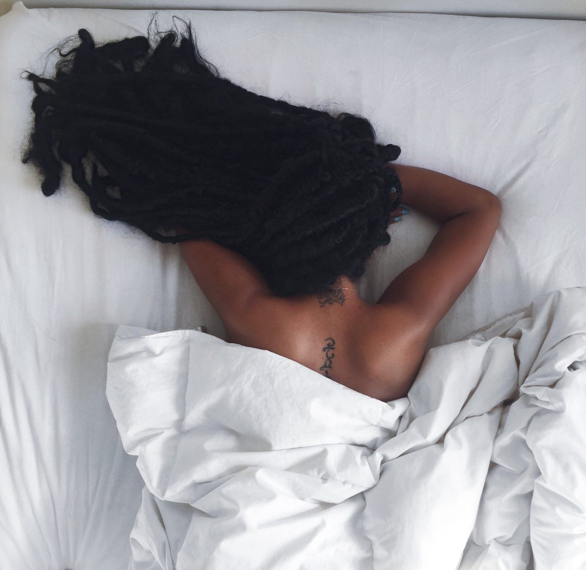 faux goddess boho locs. Back spine tattoo. blogger bed photo