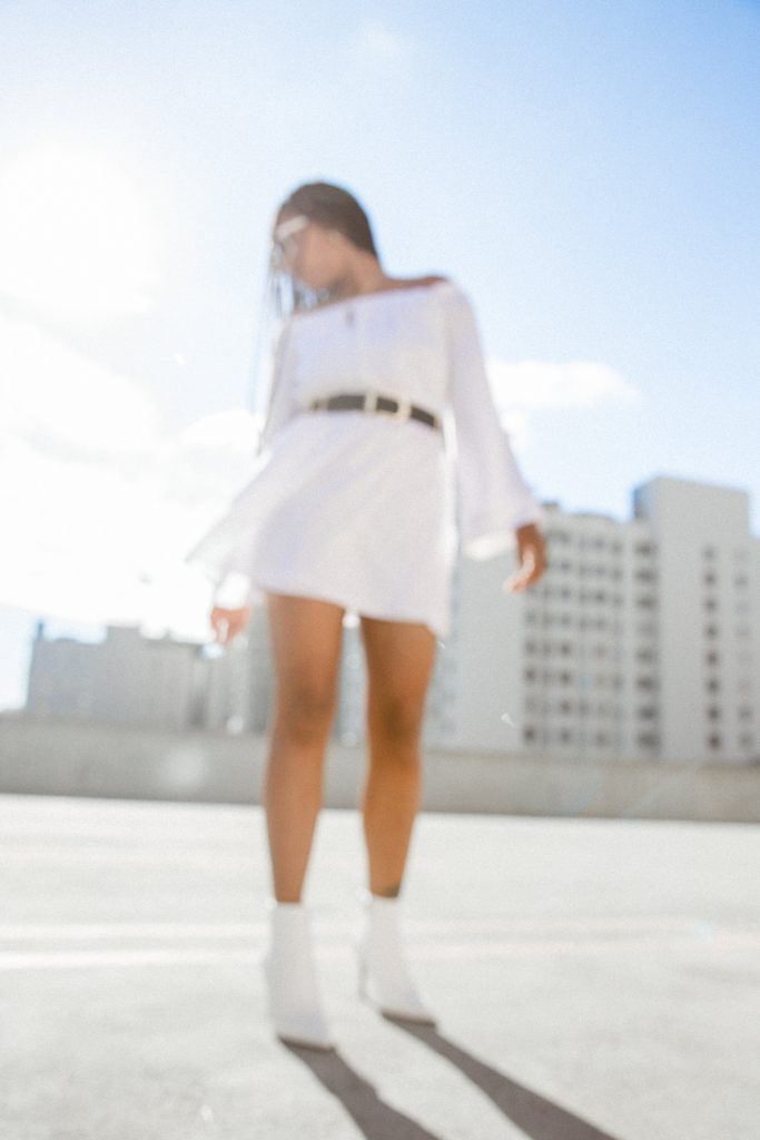 La fashion blogger photographer. Soft photography blur effect. All white boots trend