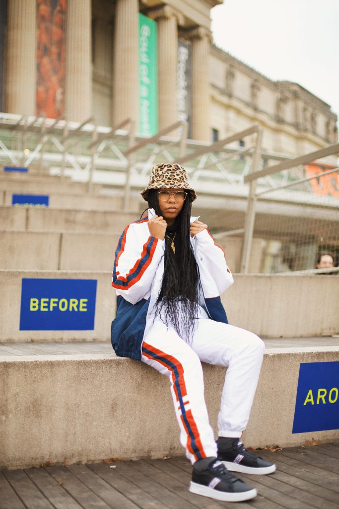 How to style track pants. Dress up athlesiure outfit with blazer ellesse USA. Brooklyn New York black girl fashion style blogger blog influencer. White track suit old school ellesse leopard print bucket hat